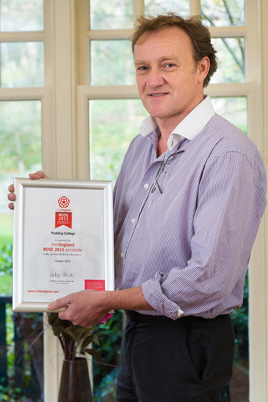 Paul Liddell, Managing Director of Lakelovers, congratulates Pudding Cottage on ROSE Award