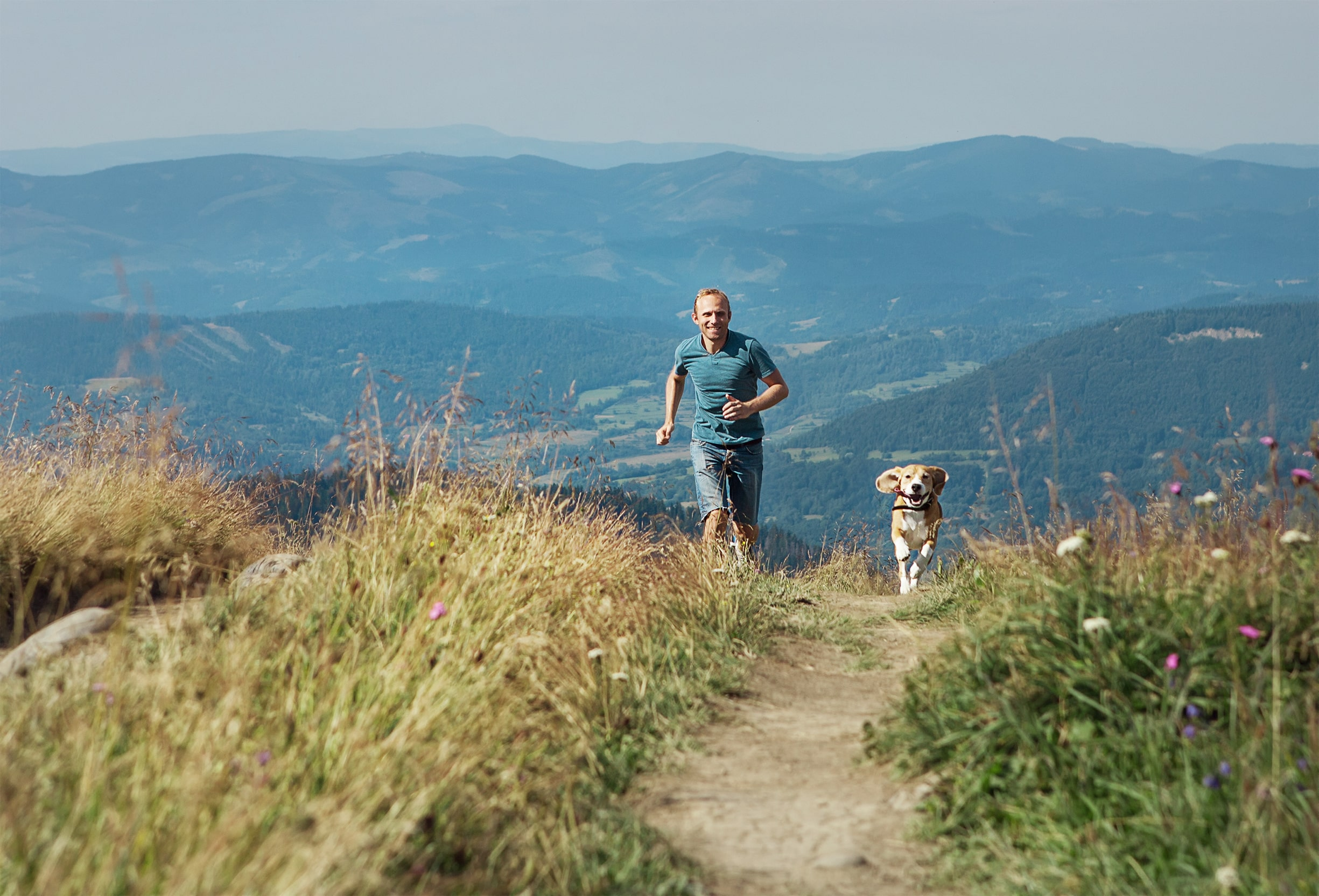 Man running with his dog on a fell in the Lake District