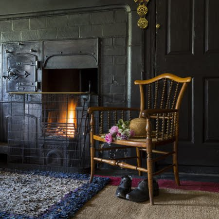 The range in the Entrance Hall at Hill Top, Cumbria with Beatrix Potter's hat and clogs. Hill Top is a typical late 17th-century Lake District farmhouse.
