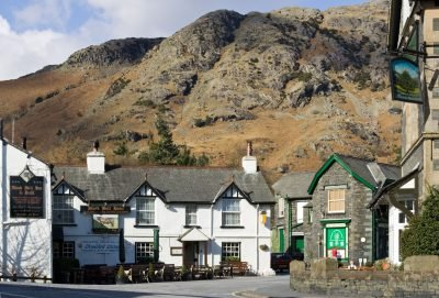 Coniston village centre and Black Bull pub with fell behind.