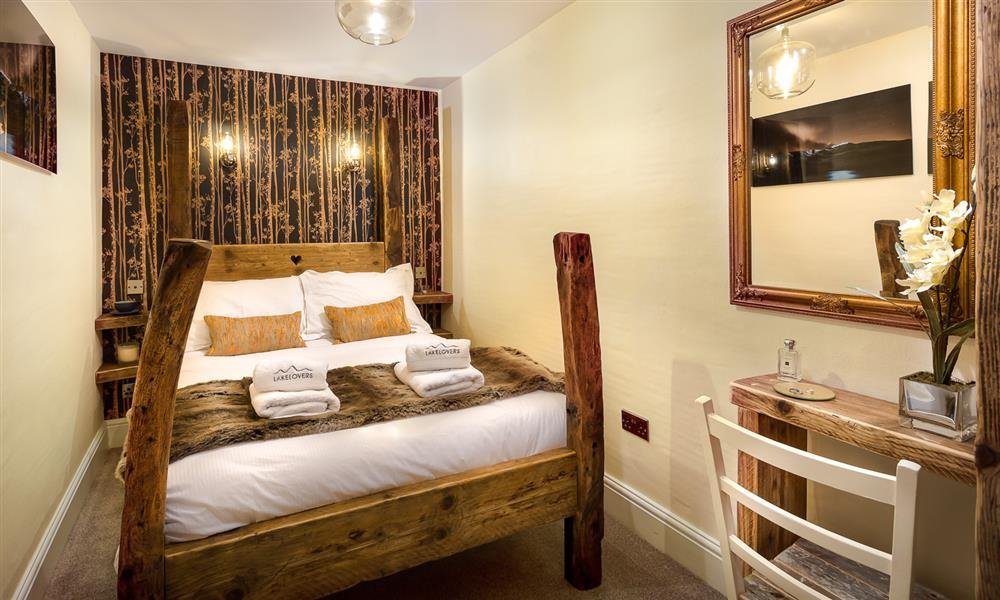 Beautiful double bedroom with natural wood bed and statement wallpaper.